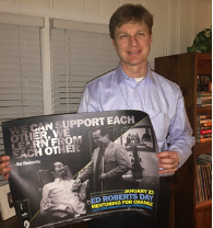 Derek holding a poster from YO with Ed Roberts and a quote: We can support each other, we learn from each others.