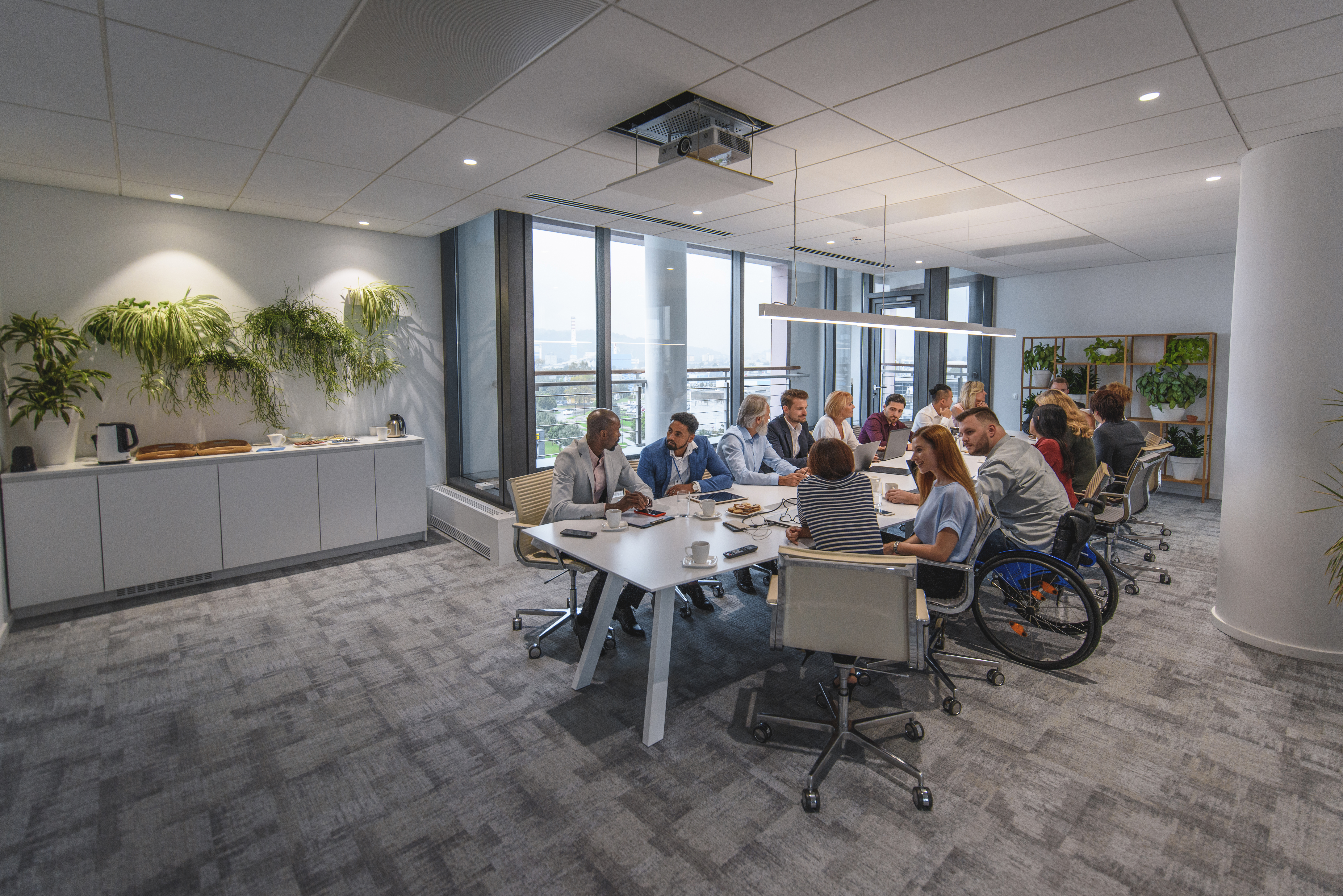 Distant view of a group of people sitting at conference table and talking with each other.