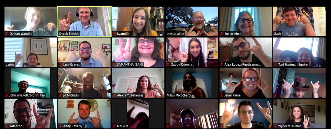 A screenshot of 28 people smiling on Zoom gallery view. Many are doing the rock-on hand symbol.